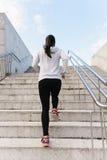 Las escaleras de funcionamiento y que suben de la mujer deportiva detrás ven imagen de archivo libre de regalías