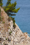 Las escaleras de piedra viejas van abajo en la roca Fotos de archivo libres de regalías