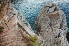 Las escaleras de piedra viejas van abajo a la agua de mar Foto de archivo libre de regalías