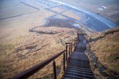 Las escaleras tragan la montaña desde arriba de la cascada islandesa en nieve del invierno y llueven, el caminar de los turistas Foto de archivo libre de regalías