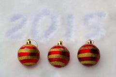 Las esferas rojas del Año Nuevo en nieve Foto de archivo