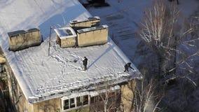 Las espadas del uso de la gente para quitan nieve del tejado de la casa durante las nevadas metrajes