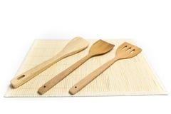 Las espadas o el lugar de madera de las aletas en la estera de bambú aislaron el fondo blanco Imagen de archivo