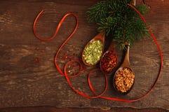 Las especias en cucharas de madera con un abeto festivo ramifican foto de archivo libre de regalías
