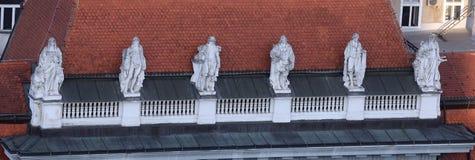 Las estatuas encima de los edificios viejos de la ciudad en la prohibición Jelacic ajustan en Zagreb fotos de archivo