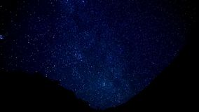 Las estrellas arrastran time lapse en el primero plano de la montaña de la silueta