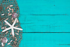Las estrellas de mar y las cáscaras blancas en la red de los pescados en la playa de madera azul del trullo firman Fotos de archivo