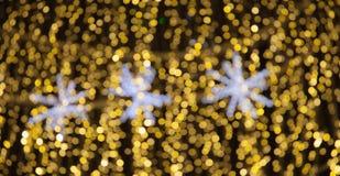 Las estrellas del oro y del blanco de Bokeh encienden el fondo de Navidad Imagen de archivo libre de regalías