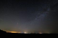 Las estrellas en cielo nocturno oscuro con la ciudad se encienden en el horizonte Imagen de archivo libre de regalías