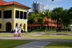 Las estudiantes del Malay recorren en los jardines atractivos del Kampong, Singapur Foto de archivo libre de regalías