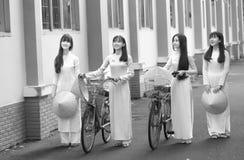 Las estudiantes llegan en uniformes de vestido largos Fotografía de archivo libre de regalías