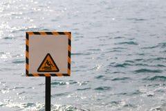 Las etiquetas de advertencia de la advertencia se guardan de resbaladizo en área de la playa Imagen de archivo