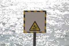 Las etiquetas de advertencia de la advertencia se guardan de resbaladizo en área de la playa Fotografía de archivo libre de regalías