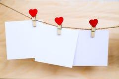 Las etiquetas engomadas del Libro Blanco que cuelgan en corazón forman los pernos y el bramante Imagen de archivo libre de regalías