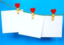 Las etiquetas engomadas del Libro Blanco que cuelgan en corazón forman los pernos y el bramante Foto de archivo libre de regalías
