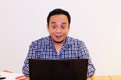 Las expresiones de los hombres asiáticos divertidos al mirar algo en su ordenador portátil foto de archivo libre de regalías