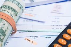 Las facturas y las cuentas, rollo de los billetes de banco del dólar, calculadora, diferencian Imágenes de archivo libres de regalías