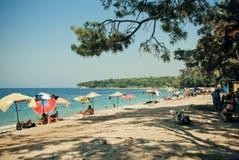 Las familias de turistas se divierten en una playa, nadando en el Mar Egeo Imagen de archivo