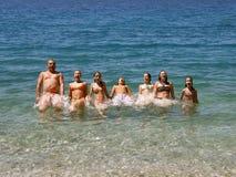 Las familias grandes, felices saltan en el mar Foto de archivo libre de regalías