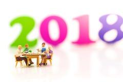 Las familias miniatura están celebrando el Año Nuevo en 2018, comiendo juntas feliz Utilizado en el concepto de festival de la fa Imagenes de archivo