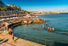 Las familias se refrescan apagado en la piscina oceánica Alberto Romano en Cascais, Portugal foto de archivo