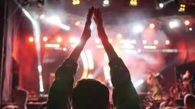 Las fans aplauden las manos y música en directo del goce en el concierto iluminado por los reflectores metrajes
