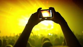 Las fans que agitan sus manos y sostienen el teléfono con los indicadores digitales almacen de metraje de vídeo