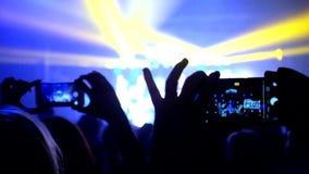 Las fans que agitan sus manos y sostienen el teléfono con los indicadores digitales almacen de video