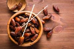Las fechas secadas del dulce dan fruto en un cuenco de madera en la tabla Foto de archivo