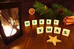 Las felices palabras de Navidad con la linterna miran al trasluz, protagonizan, rama del pino, canela y naranja Imagen de archivo libre de regalías
