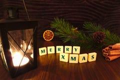 Las felices palabras de Navidad con la linterna miran al trasluz, protagonizan, rama del pino, canela y naranja Imagenes de archivo