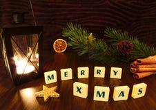 Las felices palabras de Navidad con la linterna miran al trasluz, protagonizan, rama del pino, canela y naranja Imágenes de archivo libres de regalías