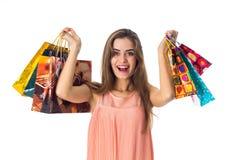 Las felices risas de la muchacha y subieron en las manos de los bolsos brillantes hermosos aislados en el fondo blanco Fotografía de archivo libre de regalías