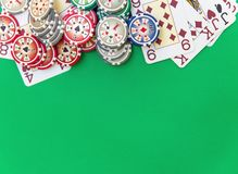 Las fichas de póker apilan y los naipes en la tabla verde imagen de archivo libre de regalías