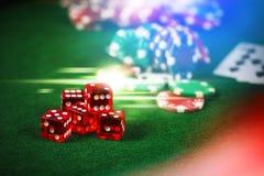 Las fichas de póker en casino juegan la tabla verde con la cuesta multi colorida Imagen de archivo