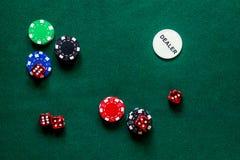 Las fichas de póker y cortan en cuadritos en un cierre verde del copyspace de la opinión de sobremesa del juego para arriba foto de archivo libre de regalías
