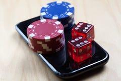 Las fichas de póker y cortan en cuadritos encima del teléfono celular Fotos de archivo