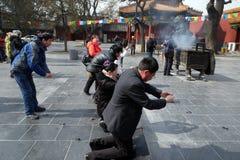 Las fieles que sostienen los palillos del incienso ruegan en Yonghegong Lama Temple en Pekín Fotos de archivo