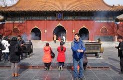 Las fieles que sostienen los palillos del incienso ruegan en Yonghegong Lama Temple en Pekín Foto de archivo