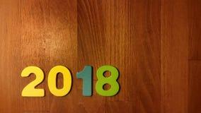 las figuras coloreadas forman el número 2018 en fondo de madera Fotos de archivo