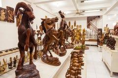 Las figuras de madera hechas a mano de Indonesain se colocan en un estante Fotos de archivo