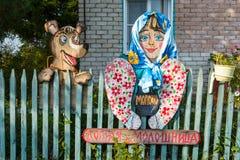 Las figuras de madera hermosas adornan la cerca de la casa rural Fotos de archivo
