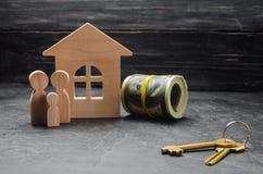 Las figuras de madera de la familia se colocan cerca de una casa de madera, de llaves y de dinero Comprando y vendiendo una casa  Fotos de archivo libres de regalías