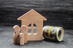 Las figuras de madera de la familia se colocan cerca de una casa de madera y de un dinero derrumbado Comprando y vendiendo una ca Imágenes de archivo libres de regalías