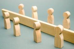 Las figuras de madera de la gente son separadas por una barrera clases sociales Competencia entre los equipos el concepto de male imagen de archivo