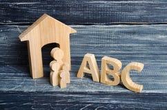 Las figuras de madera de niños se colocan en fila de pequeño a grande cerca de las letras del ABC del alfabeto inglés Fotografía de archivo libre de regalías