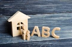 Las figuras de madera de niños se colocan en fila de pequeño a grande cerca de las letras del ABC del alfabeto inglés Imagen de archivo libre de regalías