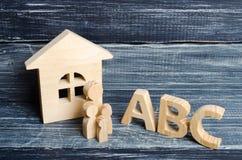 Las figuras de madera de niños se colocan en fila de pequeño a grande cerca de las letras del ABC del alfabeto inglés Imagen de archivo