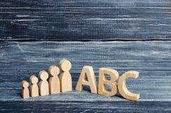Las figuras de madera de niños se colocan en fila de pequeño a grande cerca de las letras del ABC del alfabeto inglés El concepto Imagen de archivo