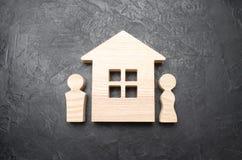 Las figuras de un hombre y de una mujer se colocan cerca de una casa de madera en un fondo concreto Marido y esposa cerca de su c Fotografía de archivo
